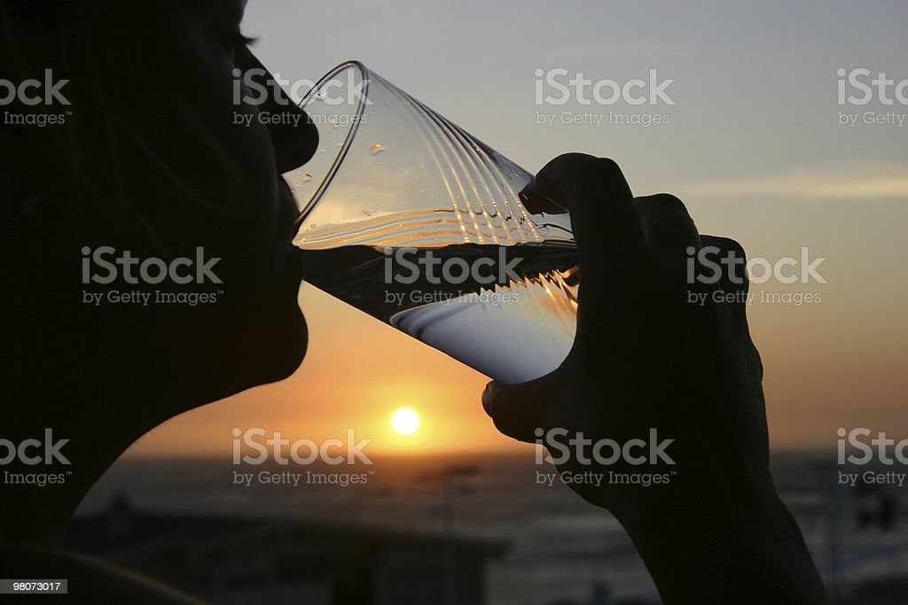 Person drinking water from glass while watching sunset royalty-free stock photo