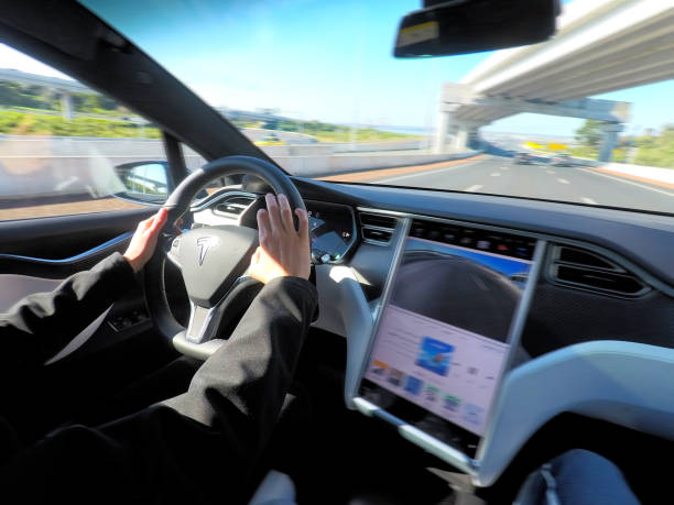 Person driving a Tesla plug-in electric car Model X on a motorway AUCKLAND - AUG 12 2018:Person drives a Tesla plug-in electric car Model X, a luxury, crossover utility vehicle (CUV) , on a motorway. in 2016 seventh among the world's best-selling plug-in cars. tesla motors stock pictures, royalty-free photos & images