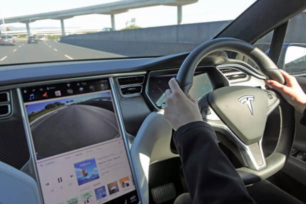 Person driving a Tesla plug-in electric car Model X on a motorway AUCKLAND - AUG 12 2018:Person driving a Tesla plug-in electric car Model X, a luxury, crossover utility vehicle (CUV) , on a motorway. in 2016 seventh among the world's best-selling plug-in cars. tesla motors stock pictures, royalty-free photos & images