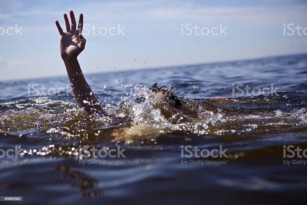 Person drowning in water with hand reached out  stock photo