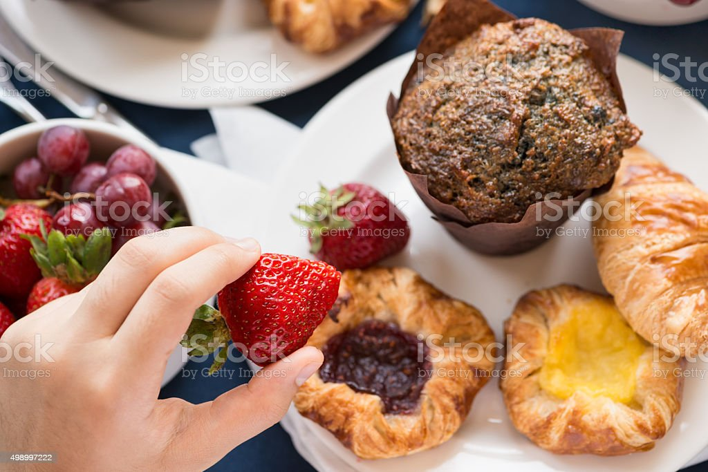 Person Eating from Room Service Continental Breakfast Tray from Hotel stock photo
