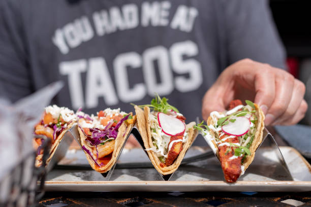 person eating tacos closeup of man eating tacos outside in summer taco stock pictures, royalty-free photos & images