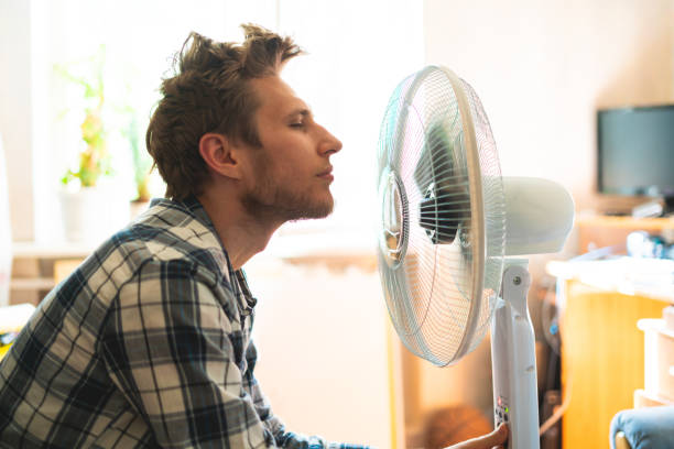 person enjoying the electric fan, cooling his face at home, during summer heat stock photo