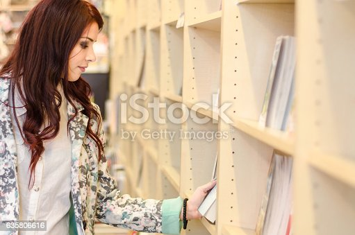 istock Person enjoys buying books at the library or bookstore. 635806616