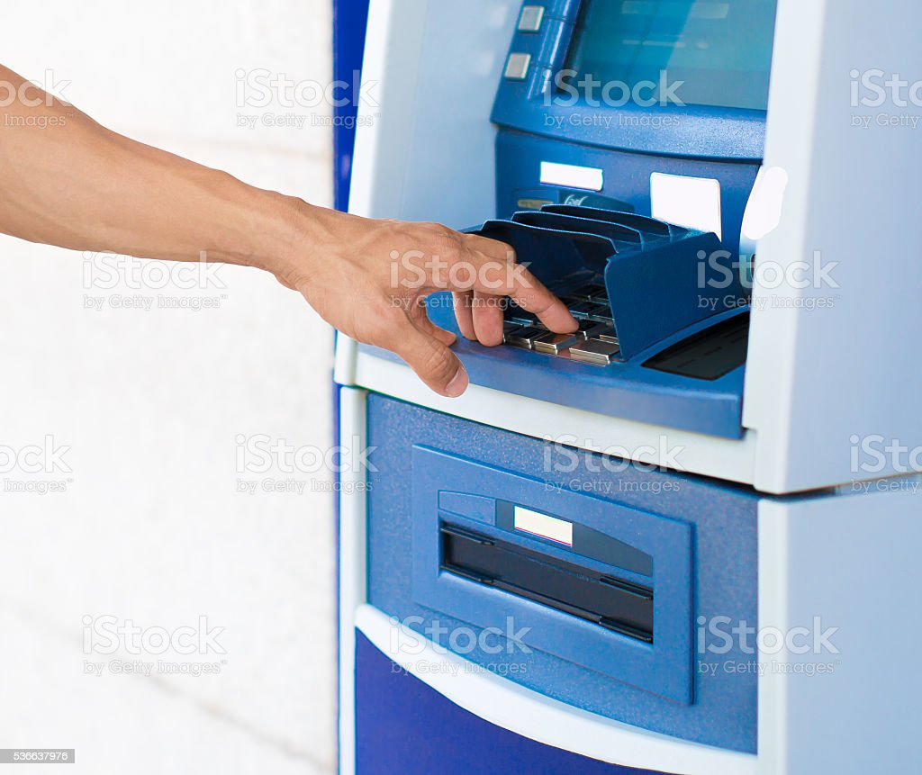 Person entering a pin number at a blue ATM machine. stock photo