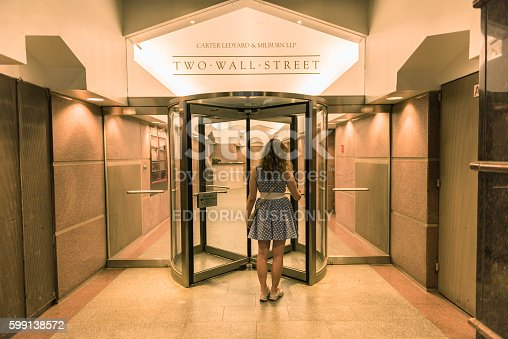New York, USA - June 18, 2016: Young woman entering two wall street building with office of Carter Ledyard & Milburn LLP