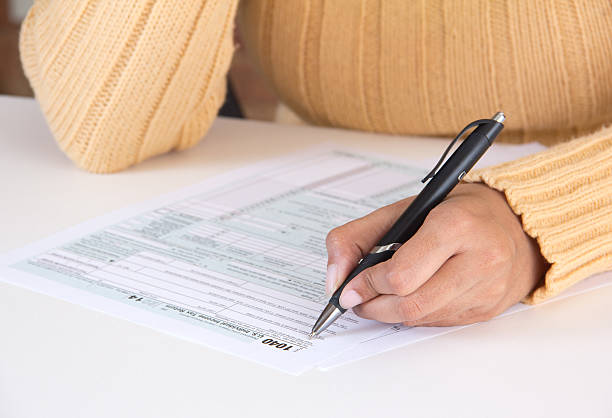 Person filing IRS tax form stock photo