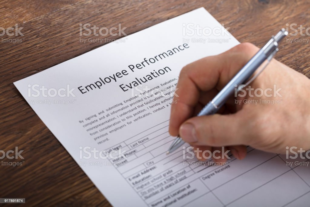 Person Filling A Performance Evaluation Form stock photo