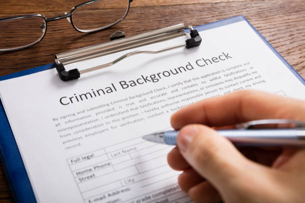 Person Filling Criminal Background Check Application Form Close-up Of Person Hand Filling Criminal Background Check Application Form criminal stock pictures, royalty-free photos & images
