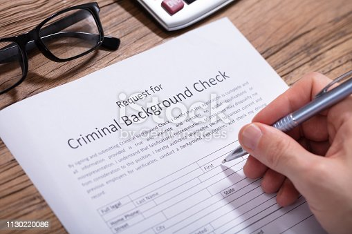 istock Person Filling Criminal Background Check Form 1130220086