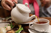 Person filling cup of tea in a cafe