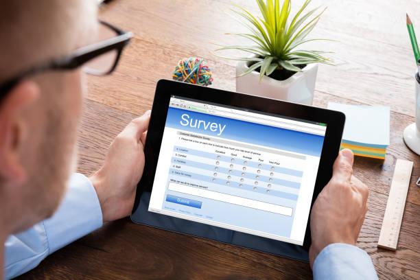 Person Filling Online Survey Form On Digital Tablet stock photo