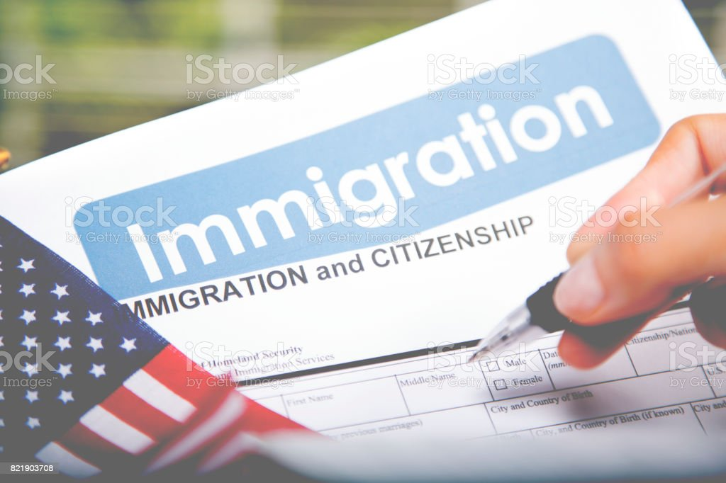 Person filling out American immigration, citizenship forms. USA flag. stock photo