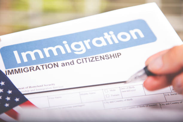 Person filling out American immigration, citizenship forms. USA flag. - foto stock