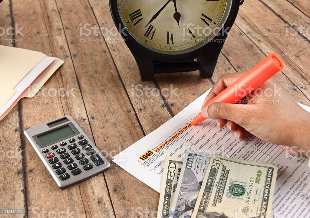 Person filling tax returns before deadline stock photo
