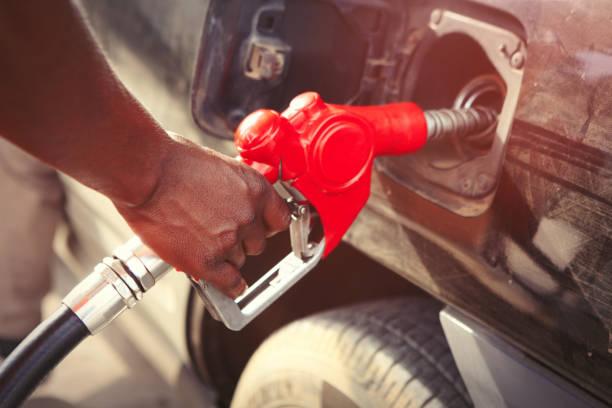 Person füllt den Tank eines Autos – Foto