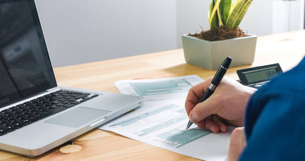 Person filling US tax form stock photo