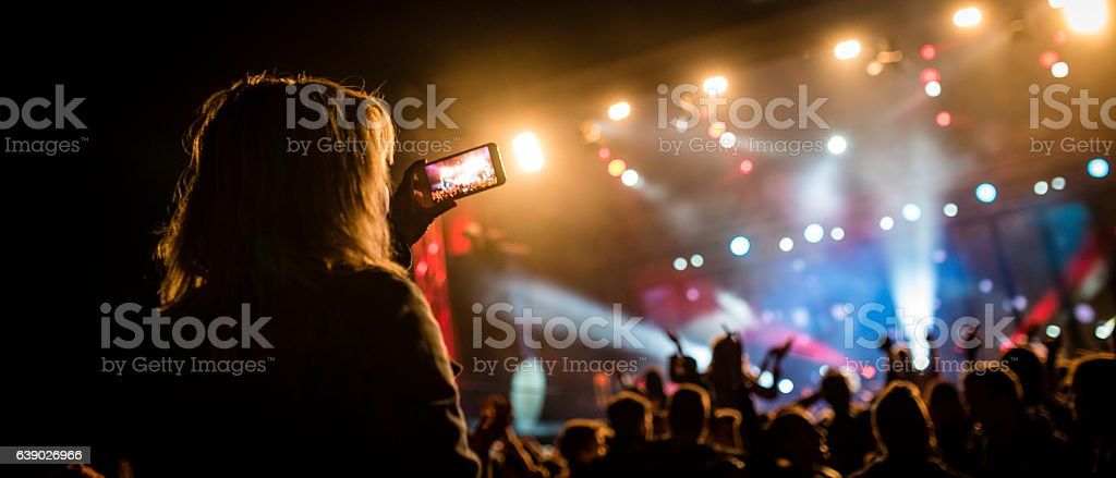 Person filming a concert stock photo
