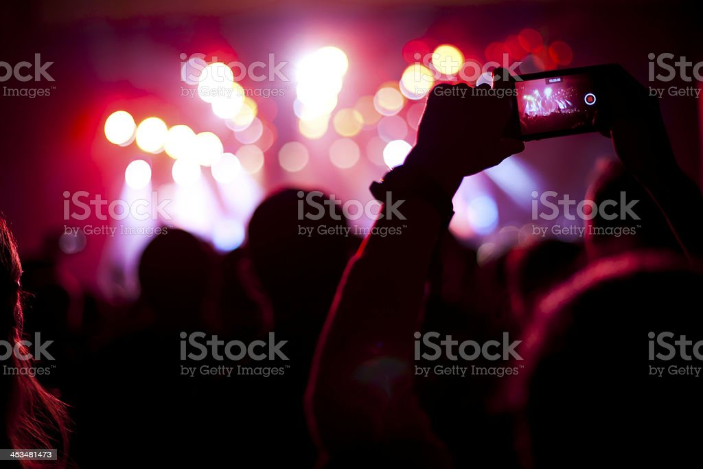 Person filming concert with blurry lights and people stock photo