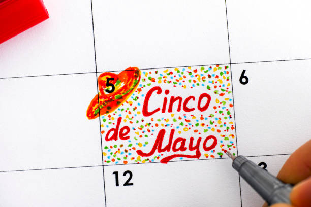 person fingers with pen writing reminder cinco de mayo in calendar. - cinco de mayo stock photos and pictures