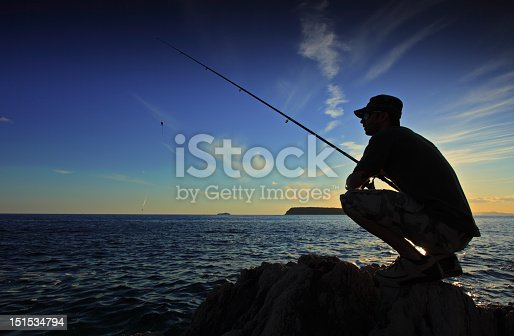 istock Person fishing during the sunset on a vast body of water 151534794