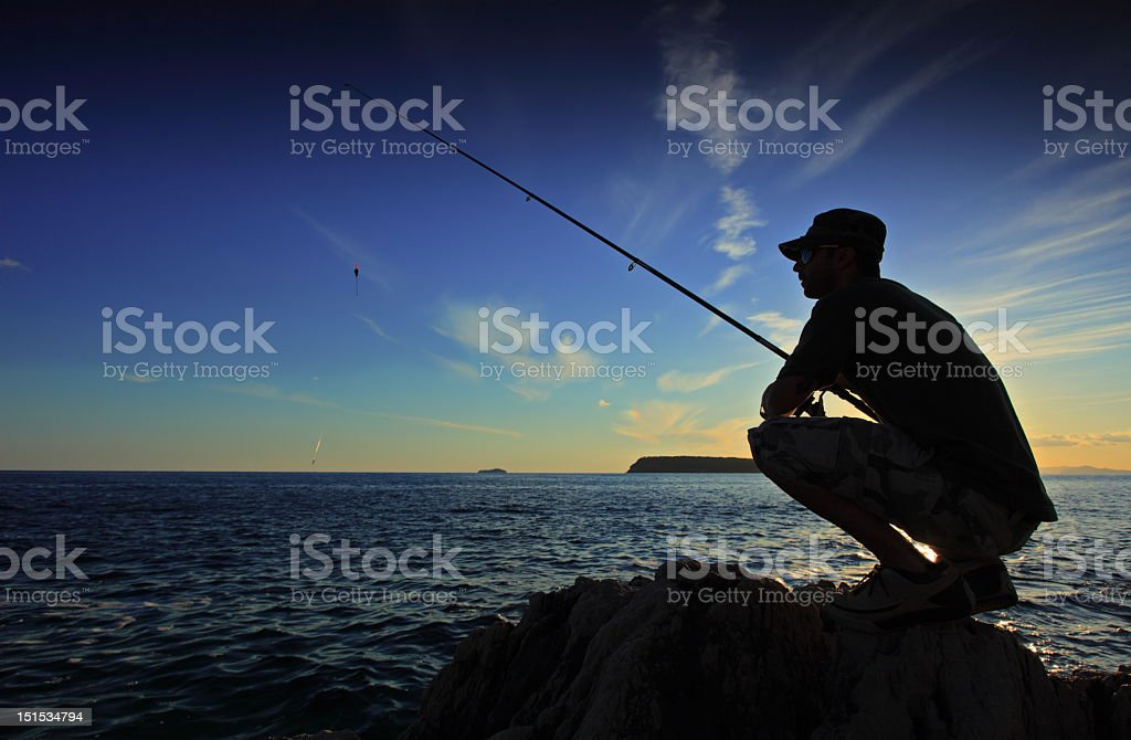Person fishing during the sunset on a vast body of water stock photo