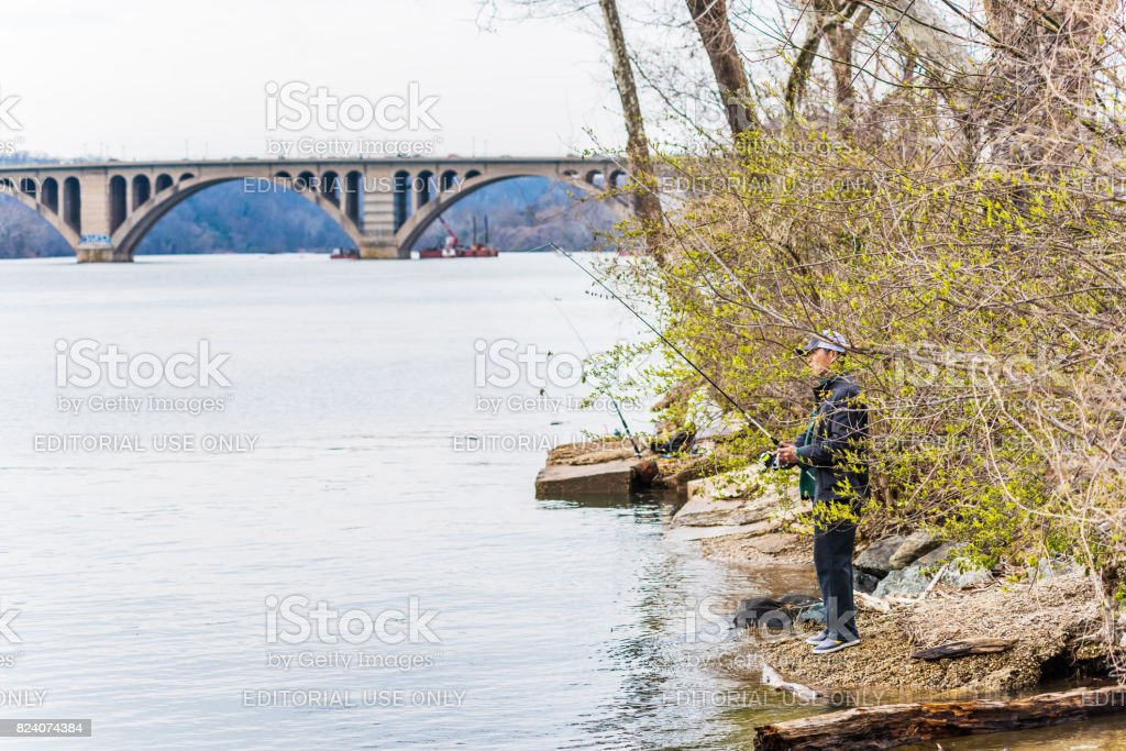 Person fishing on riverfront in Georgetown with key bridge in potomac river stock photo
