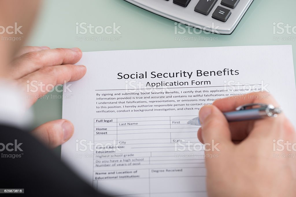 Person Hand Filling Social Security Benefits Form stock photo