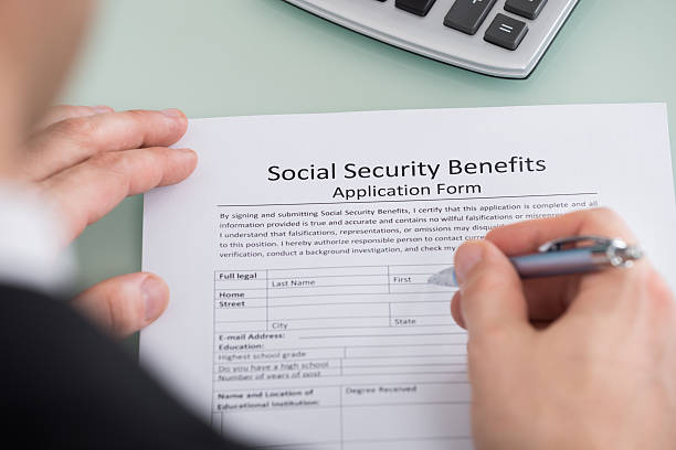 Person Hand Filling Social Security Benefits Form Close-up Of Person Hand Filling Social Security Benefits Form social security stock pictures, royalty-free photos & images