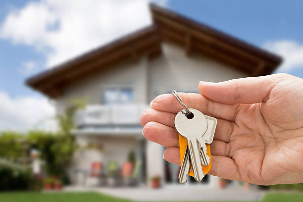 Person Hand Holding House Key stock photo