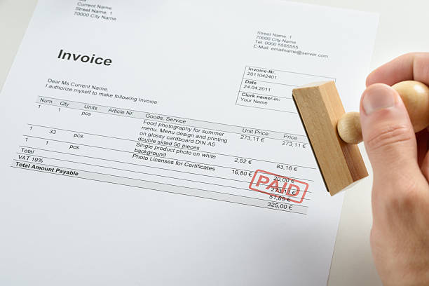 person hand holding rubber stamp over paid invoice - paid stock pictures, royalty-free photos & images