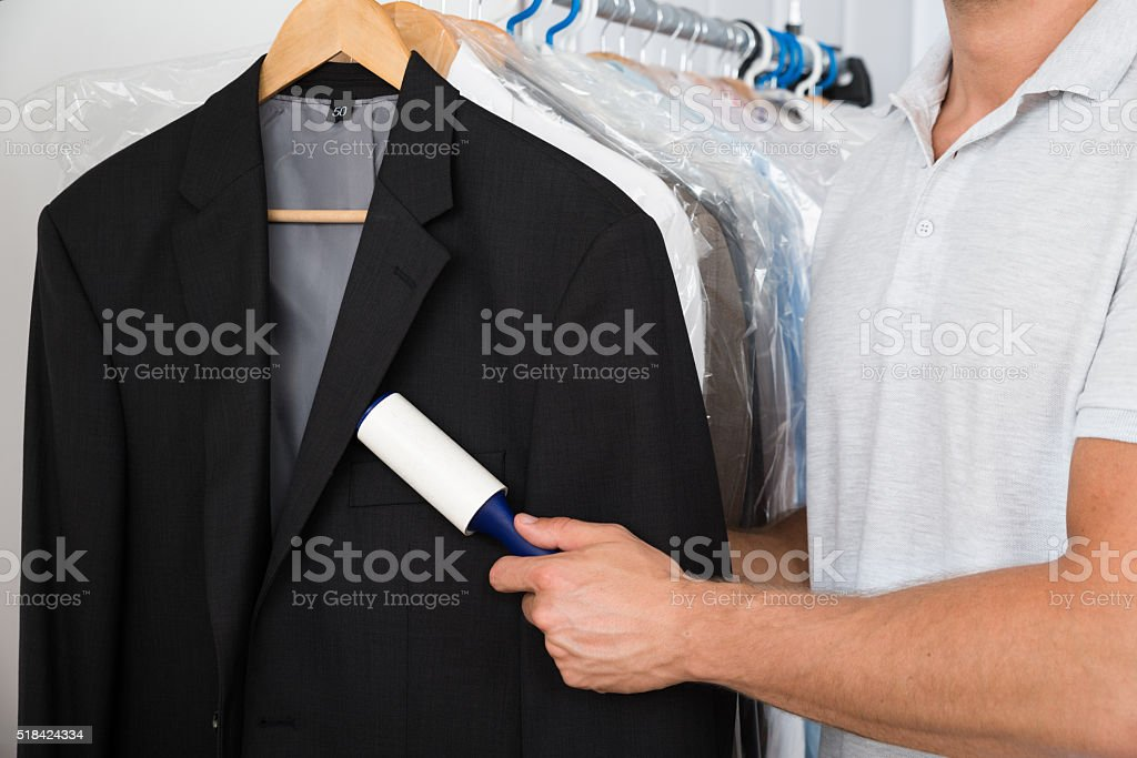 Person Hand Removing Dust With Lint Roller stock photo