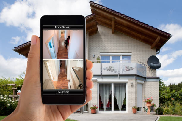 Person Hand Using Home Security System On Mobile Phone stock photo
