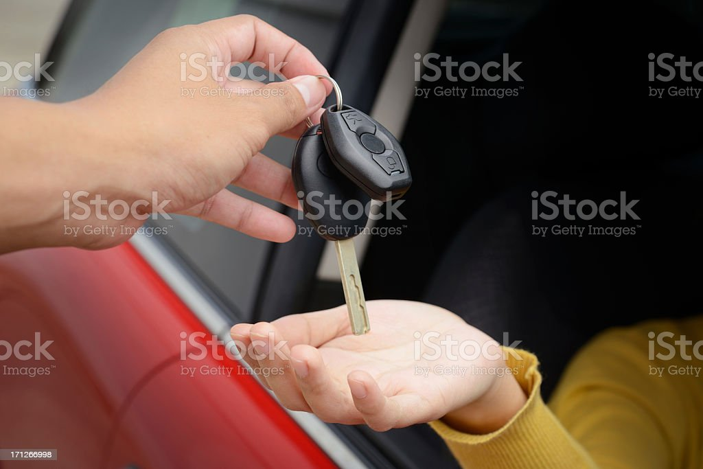 Person handing over car keys to a driver in a red car royalty-free stock photo