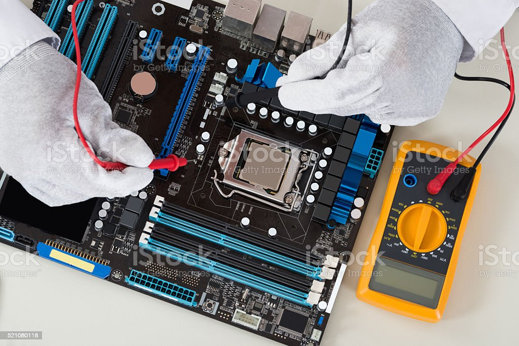 Person Hands Checking Motherboard With Multimeter stock photo