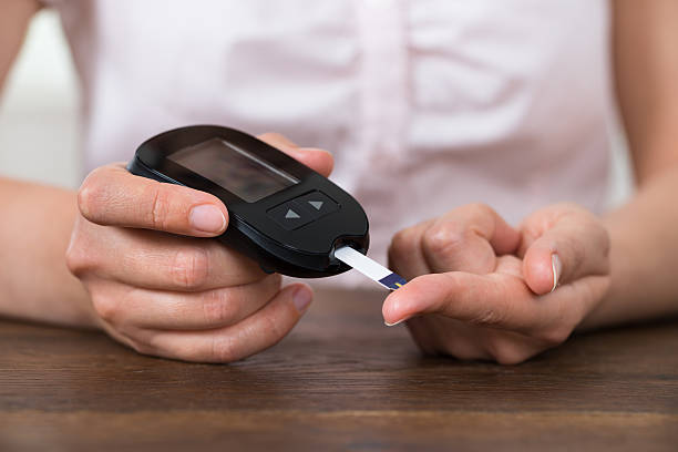 person hands holding glucometer - diabetes stock photos and pictures