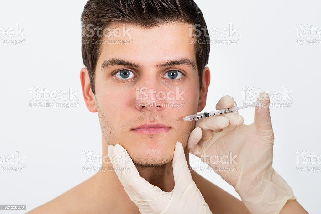 Person Hands Injecting Syringe On Man Face stock photo