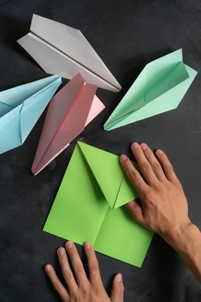 person hände machen eine origami farbe papierebene - origami anleitungen stock-fotos und bilder