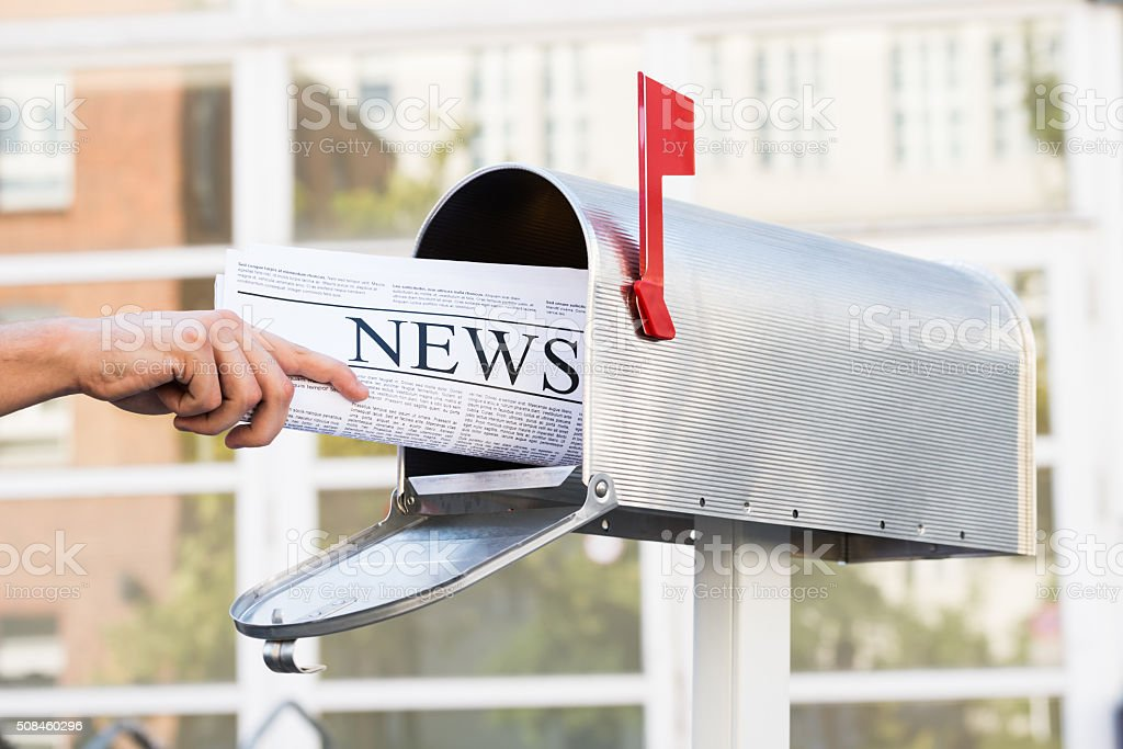 Person Hands Opening Mailbox To Remove Newspaper stock photo