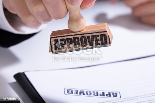 854317150istockphoto Person Hands Using Stamper On Document With The Text Approved 917895520
