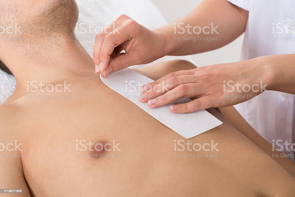 Person Hands Waxing Man's Chest stock photo