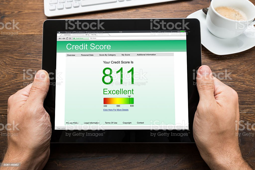 Person Hands With Digital Tablet Showing Credit Score stock photo