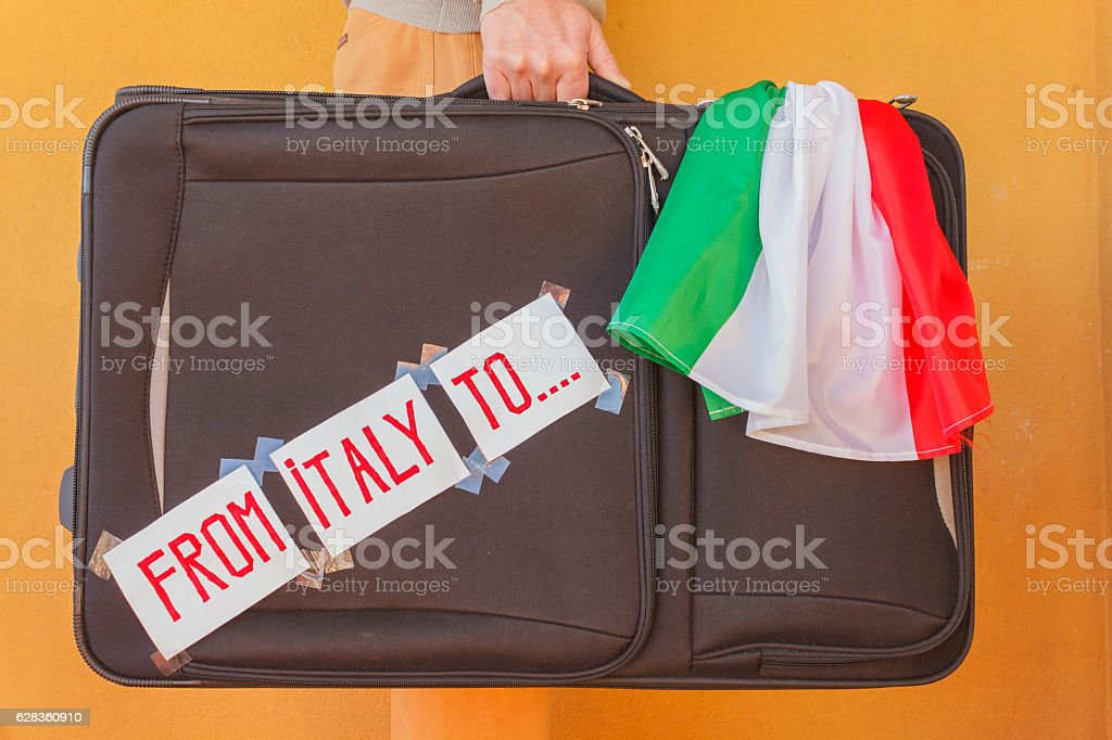 person has a suitcase in hand to emigrate from Italy stock photo