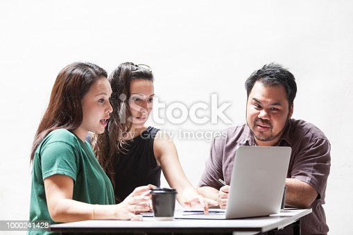 3 person having a discussion infront of a laptop
