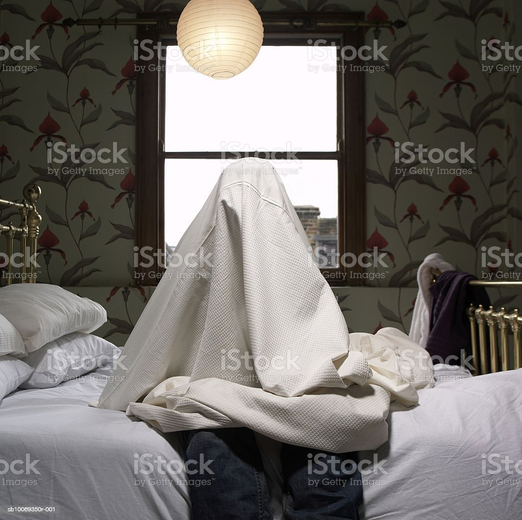 Person hiding under sheet on bed royalty-free stock photo