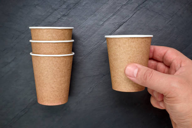 Person holding a recyclable cardboard cup on a black slate background stock photo