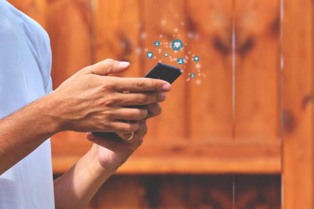 persona sosteniendo un smartphone con actividad en redes sociales suscriptores, me gusta, mensajes - social media fotografías e imágenes de stock