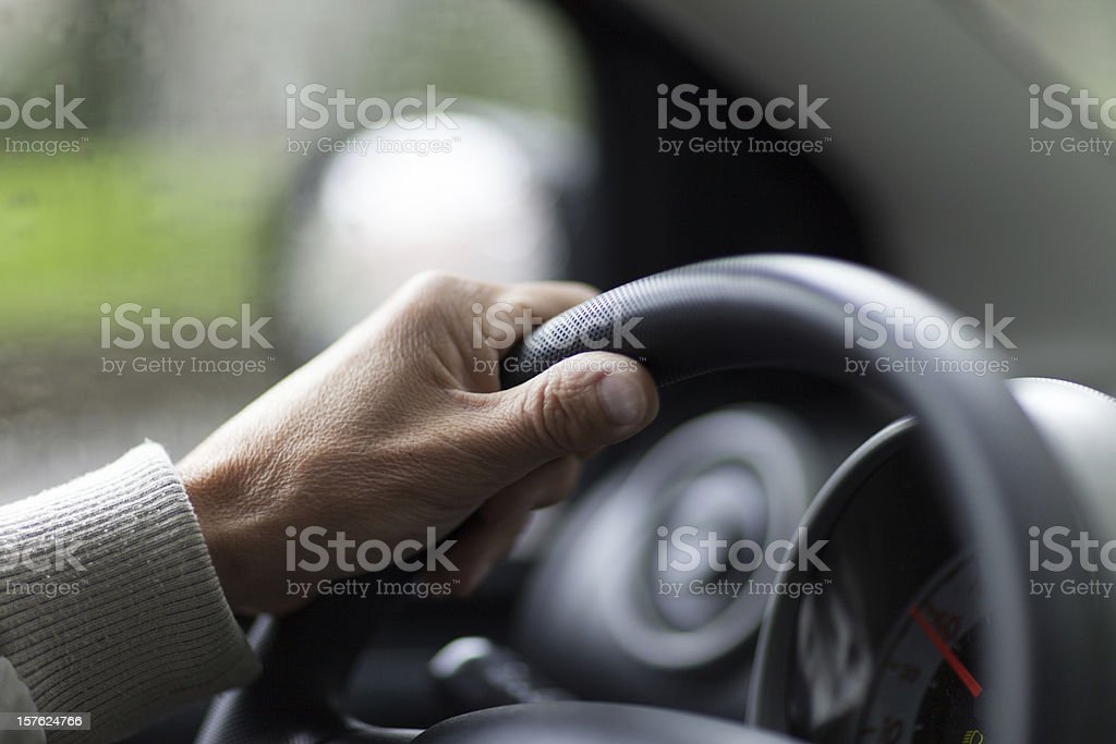 A person holding a steering wheel in a vehicle stock photo
