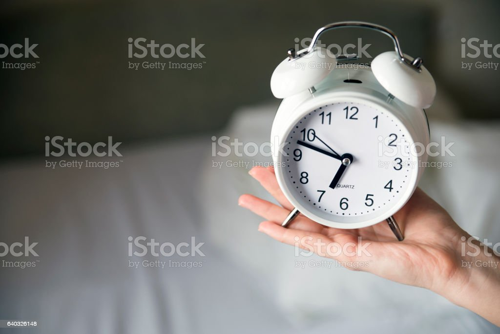 Close up hold alarm clock on white bed in the morning by woman hand...