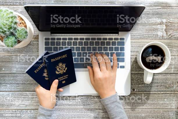 Person holding an american passports while using a laptop picture id1069846188?b=1&k=6&m=1069846188&s=612x612&h=r4dqvp7i6ypni9pxtgqnis7zg ecmrcizfonr3fxhpe=